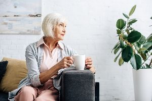 Old Woman Having Coffee In Her Apartment